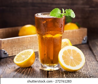 glass of ice tea with mint and lemon on wooden table