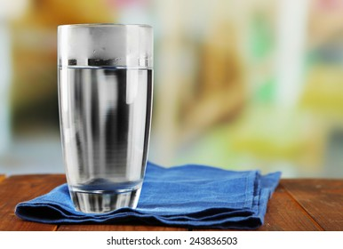 Glass of ice water with napkin on wooden table and light blurred background
