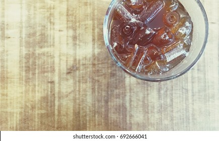 glass of iced black coffee on wooden table with top view in pale brown dramatic color and copy space on the left hand