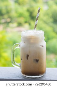 Glass of Iced coffee latte on balcony edge with outdoor natural green background
