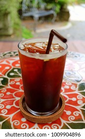 Glass of Iced Coffee on the Colorful Table at Garden Terrace with Selective Focus