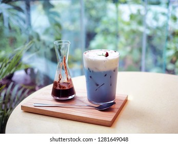 A glass of iced dark cocao with blue milk mint; one side is dark bitter cocao the other is pastel blue mint with milk froth. Blur background with selective focus.