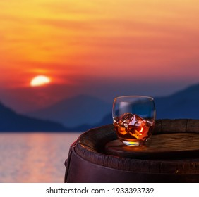 Glass of iced dark rum on oak barrel. Red beautiful sun going down over the sea at the background.