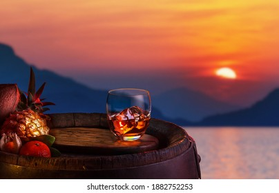 Glass of iced dark rum and tropical fruits over oak barrel. The red beautiful sunset sky at the sea shore.