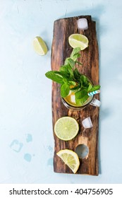 Glass of Iced green tea with lime, lemon, mint and ice cubes on wooden chopping board over light blue textured background. Flat lay. With copy space. Focus on mint