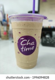 """a glass of iced latte drink with the """"chatime"""" brand with the background of office stationery. photo taken on 7 June 2021 in Jakarta"""