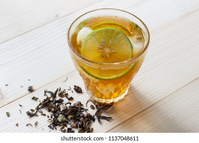 Glass of iced tea with lime slices.