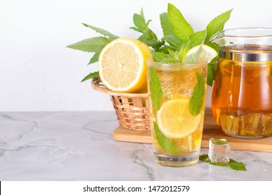 Glass of iced tea with mint and lemon on marble table. Cold drink. Copy space