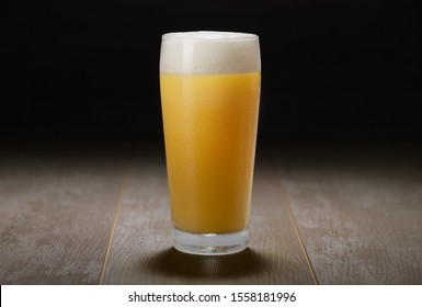 A glass of India Pale Ale, hazy unfiltered juicy draft beer on wooden surface and black background