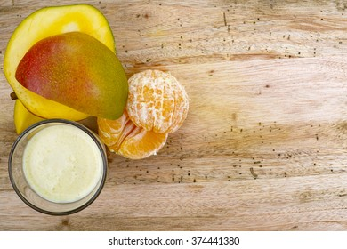 Glass Indial traditional drink sweet lassi with mango and orange on wooden background, copy space