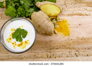 Glass indian traditional lassi with spices, coriander, ginger, turmeric and cardamom on wooden background, copy space