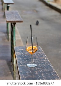 glass with inside orange coktail on top a wooden rail
