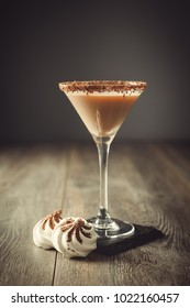 Glass of Irish cream liqueur drink in a glass with chocolate rim with mini meringues on slate coaster
