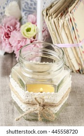 Glass jar with candle inside decorated with lace and string.