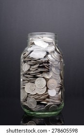 Glass jar with coin isolated on black background
