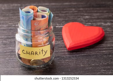 Glass jar with coins and euro notes with the inscription CHARITY. With a huge red heart on an old black wooden table. The concept of kindness and help those in need.