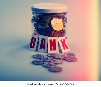 Glass jar with coins and inscription bank on a light background