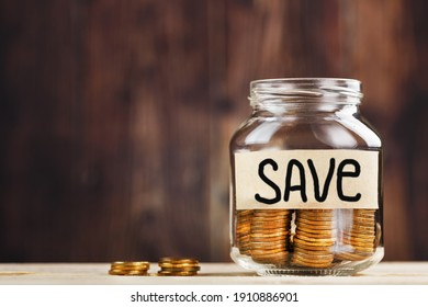 A glass jar with coins and the inscription SAVE on a wooden table. Budget for investing in the future