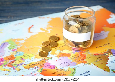 Glass jar with coins on world map