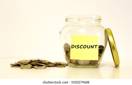 Glass jar with coins for savings. The inscription DISCOUNT on the note paper. Financial concept.