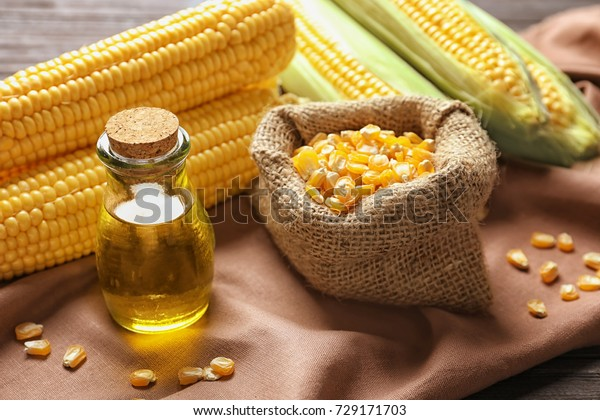 Glass jar with corn oil and dried kernels on fabric