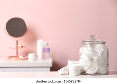 Glass jar with cotton pads on table in bathroom, space for text
