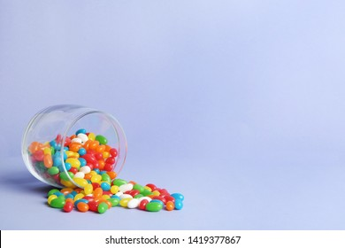 Glass jar with delicious bright jelly beans on color background. Space for text