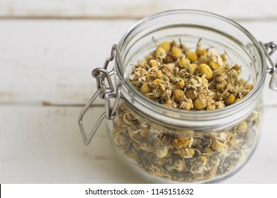 Glass jar with dried chamomile tea on wooden kitchen table. Herbal tea. Healthy drink