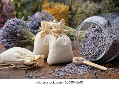 Glass jar of dry lavender flowers, sachets, bunches of dry lavender. Jars of different dry medicinal herbs on background. Alternative medicine.