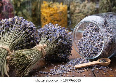 Glass jar of dry lavender flowers, bunches of dry lavender. Jars of different dry medicinal herbs on background. Alternative medicine.