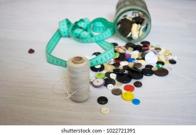 glass jar falling down on the floor and buttons spill away
