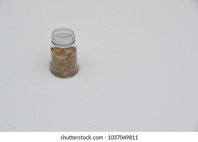 a glass jar filled with birdseeds standing in a layer of snow