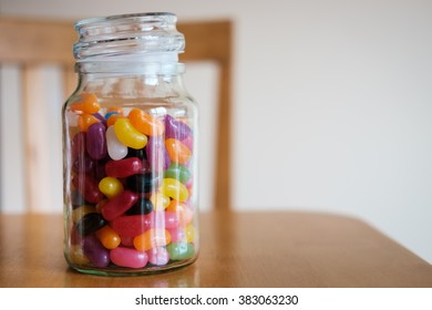Glass jar filled with jellybeans, lid open and sitting on table with chair in background.