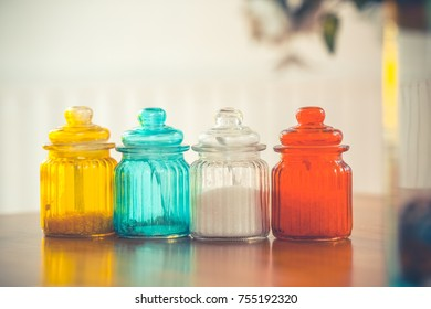 Glass jar filled with sugar on wooden boards.