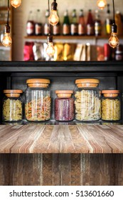 Glass jar filled with various pasta on wooden table with retro bulb lamp in vintage kitchen