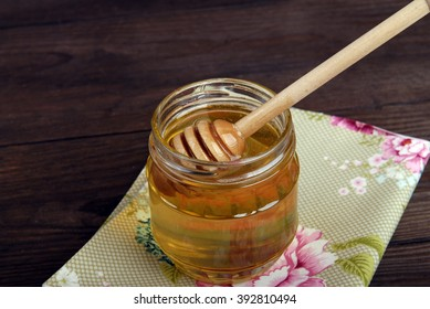 Glass jar with floral honey on a napkin on a wooden background.