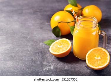 glass jar of fresh orange juice with fresh fruits on dark table.