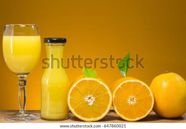 glass jar of fresh orange juice and fresh fruits on orange background