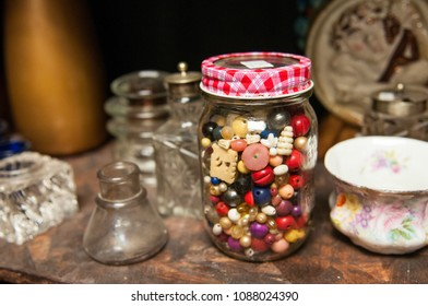 glass jar full of beads and buttons with glass and ceramic items on wood surface