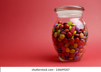 Glass Jar full of bright colorful lollies and candy with closed lid against a red orange background with copy space for your text here.
