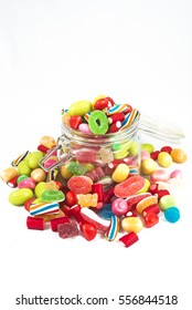 Glass jar full of candies isolated in white background.