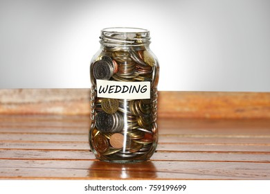 A glass jar full of coins to represents wedding concept- with masking tape and wedding written on it.
