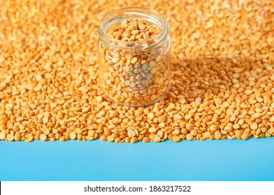 Glass jar full of dried grain of peas on blue background. Copy space