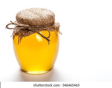Glass jar full of honey on a white background