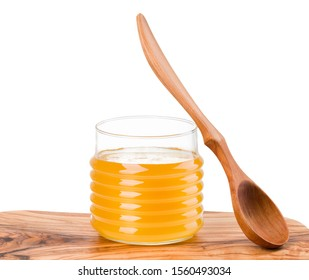 Glass jar full of honey and wooden fork on wooden plank isolated on white background with clipping path