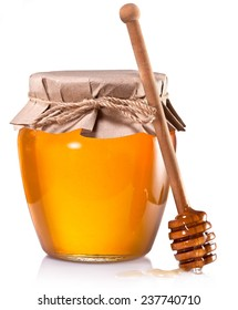 Glass jar full of honey and wooden stick on a white background.