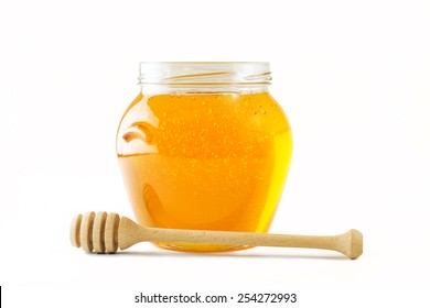Glass jar full of honey wooden honey dipper