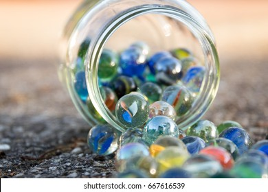 Glass jar full of marbles, fallen on the street. View of jar at an angle. Bright picture, with blue as main color. Front and background blurred. Other colors red, green, yellow.