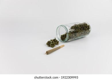 Glass jar full of marijuana buds, dried marijuana flowers and a marijuana cigarette. Isolated on white background. Sweet addiction