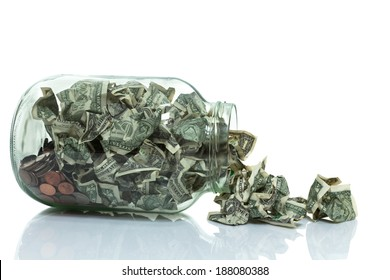 Glass jar full of money tipped over on its side spilling money